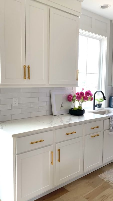 Beautiful custom white kitchen with Cloe tile and custom dark island.  Decorated with pictures, kitchen accessories, flowers, cutting boards, vases, urns, containers.    #LTKSeasonal #LTKhome #LTKsalealert