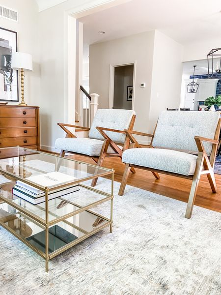 A brass and glass coffee table next to some mid-century accent chairs.  Living room ideas, home decor, accent chairs, mid century design, coffee table, glass coffee table, living room furniture  #LTKhome