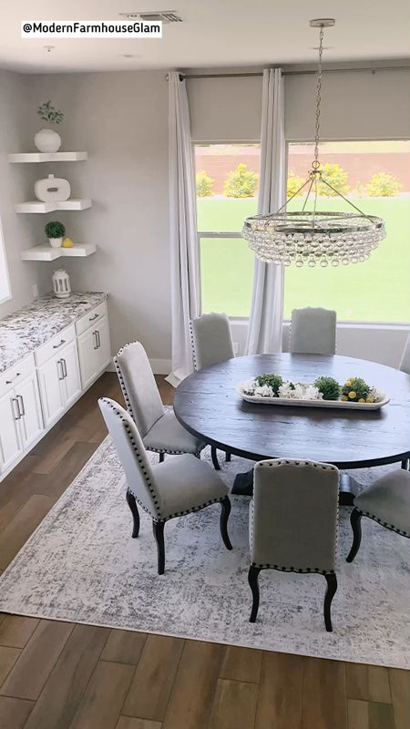 My modern farmhouse glam kitchen dining room area. Round dining room table, neutral area rug, crystal chandelier, dining room chairs, curtains.   #LTKDay #LTKhome #LTKsalealert