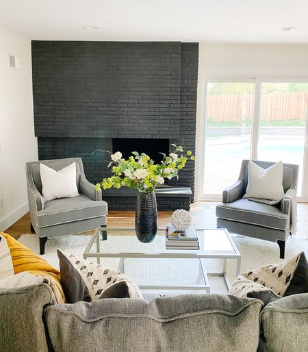 Pair of gray accent chairs in the living room with a painted brick fireplace  Accent chairs, living room decor, living room chairs, home decor, gray chairs, coffee tables  #LTKhome