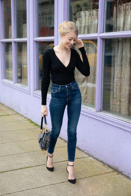 Black knit ribbed wrap long sleeved top  Blue ankle Jeans  Dior saddle bag in navy oblique canvas  Transitional spring outfit  #LTKunder100 #LTKsalealert #LTKunder50   #LTKshoecrush #LTKSeasonal #LTKitbag