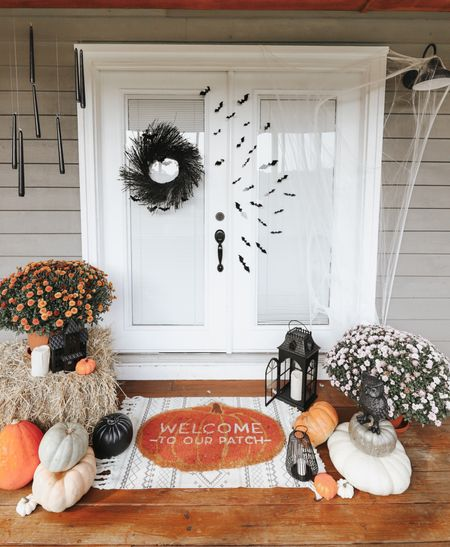 Spooky Halloween front door decorations with mums, pumpkins, haunted houses, bats and floating black candles. 🦇  #LTKSeasonal #LTKhome #LTKHoliday