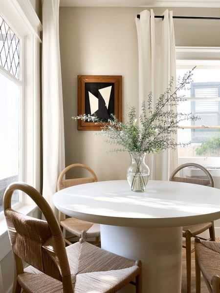 Organic curved wood and cord dining chairs paired with a modern, white concrete table and statement art - it's all about contrast! I've also linked several chair options that offer a similar look and feel, at varying price points.  #LTKhome
