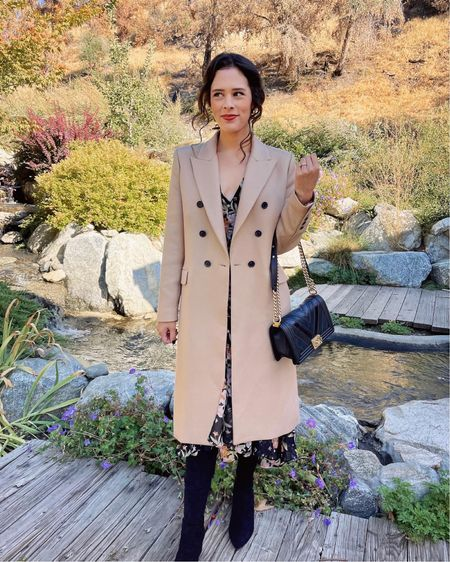 Fall wedding guest style: a classic camel coat 🧥 layered over a dark floral dress. Pair this look with over-the-knee boots for extra warmth! This boots from Goodnight Macaroon are one of my favorites—super comfy and they stay put over my knees. 👢 (Fall style. Fall fashion. Fall outfit)  #LTKwedding #LTKshoecrush #LTKstyletip