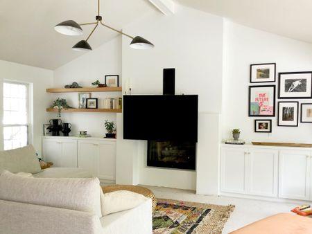 The perfect solution for mounting a tv over your fireplace!   #livingroomdecor #tvmount #layeredrugs #floatingshelves #livingroomlight  #LTKhome #LTKunder100