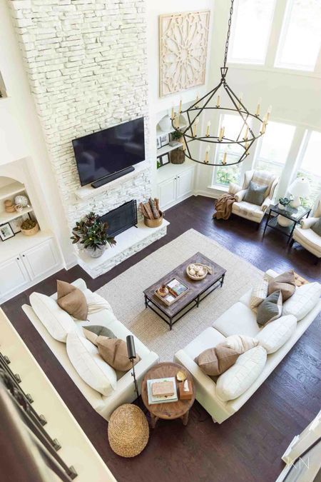 Bird's eye view of my two story living room dressed for fall. Home decor living room decor fall decor pottery barn sofa iron chandelier large wood art wingback chair coffee table styling jute rug fall pillows cozy throw   #LTKhome #LTKstyletip #LTKSeasonal