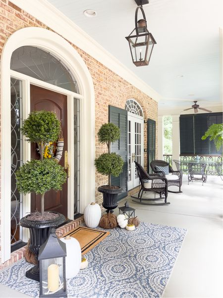 Porch with fabulous faux topiaries, oversized rug and pumpkins to create a welcoming entrance!   #LTKhome #LTKSeasonal #LTKstyletip