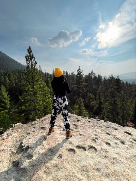 Holiday hiking outfit! Great gift ideas for your outdoorsy friends and family. Cutout mock neck crop top, cow print pants, tan Columbia hiking boots and a yellow beanie.   #LTKGiftGuide #LTKtravel #LTKHoliday