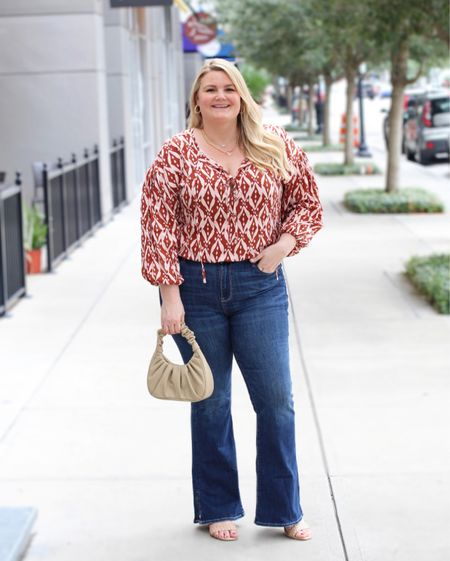 """Flare jeans from American Eagle. I'm wearing the long/tall length (I'm 5'9""""). Size down if in between sizes. They do have stretch, are high rise, and super comfy. Shibori print top available in sizes 14 and up. Wearing the 14, TTS. Scrunch handle bag is only $15!   #LTKitbag #LTKunder50 #LTKcurves"""