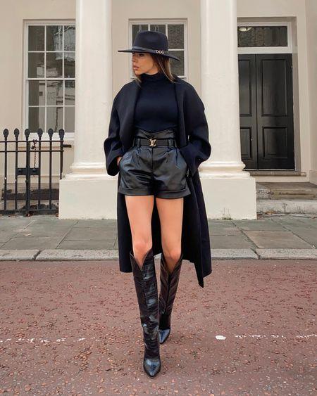 Black leather shorts, black knee high boots, black fedora, black coat