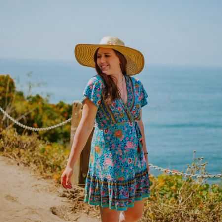 Tan sun hat, straw bag, gold moon necklace, floral wrap dress, tan espadrilles.  My gold moon necklace is on sale for $12!  This look is linked on the LIKEtoKNOW.it shopping app. You can access via the link or nomadicniche.com under style.  http://liketk.it/2Qhrw #liketkit @liketoknow.it