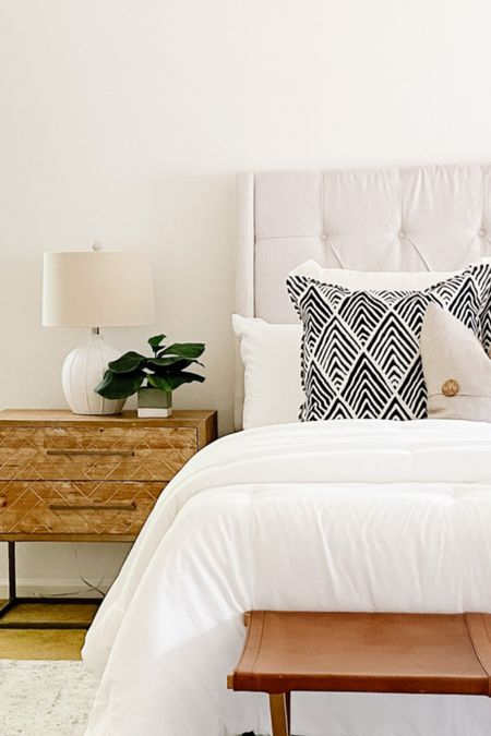 A pair of light wood nightstands stands out against the cream headboard and white bedding.  Nightstands, bedroom decor, bedroom furniture, side tables, neutral headboard  #LTKhome