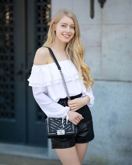 Black leather shorts White flowy off the shoulder top Black leather sandals mid heel Chanel small boy with pearls  Spring summer edgy classic style  #LTKitbag #LTKSeasonal #LTKeurope