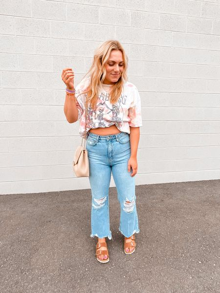Oversized tie dye graphic tee Cropped flare jeans Big buckle Birkenstocks Crossbody purse   #LTKshoecrush #LTKstyletip #LTKunder100