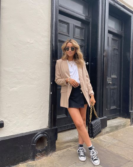 Simple transitional style - wearing denim skort with a camel blazer and classic white tee, styled with black hi top converse   #LTKeurope #LTKSeasonal #LTKunder50