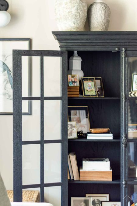 My black glass front cabinet is styled with family mementos and special family photos. Home decor cabinet styling picture frame bird print pair decorative box  #LTKhome #LTKstyletip #LTKfamily