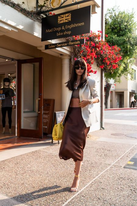 Go-to chic and timeless outfit: silk midi skirt paired with a matching bra top and oversized neutral blazer over it. For accessories, wearing white Amina Muaddi sandals and mustard yellow Bottega Veneta clutch   #LTKshoecrush #LTKstyletip #LTKitbag