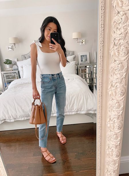 """Straight leg jeans // casual summer outfit  •Express white tie strap body suit size xxs - on sale for 25% off, comes in 4 neutral colors and was just restocked in white!  •Levi's wedgie fit ankle jeans in """"shut up"""" wash size 24. Fit note: the bens have been cut with scissors to shorten   •J.Crew brown strappy sandals size 5.5  •Polene bucket bag   #LTKSeasonal #LTKsalealert"""