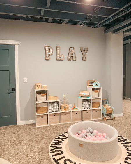 Modern farmhouse basement playroom ✨ #playroomdesign Our toy organization system is simply these two $40 cube organizers put together! It's such a simple way to save money and has lasted. We are always rotating out her toys and putting the latest Montessori + wooden toys on top. We store all her other current favs in the cubes! Storage bins are all from Amazon and Target — Linking exact playroom decor and toys here #targetstyle #amazonfinds #playroom #modernfarmhouse #targethome #storagesolutions #farmhousestyle #ballpit #woodentoys #playroomstorage #mommyblogger #playroomorganization   #LTKkids #LTKfamily #LTKhome