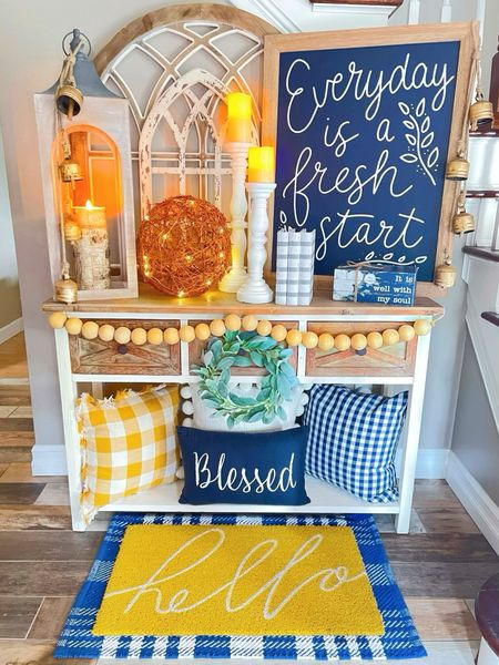 """Create your very own """"Everyday is Fresh Start"""" entryway with weathered white farmhouse arches, a glowing lantern, a twinkling grapevine sphere, welcome mats, cozy pillows, stamped farmhouse decorative books, wood bead garland, and a beautiful uplifting sign reminding you that each new day is the chance at a fresh start.  Fresh starts are like the morning sun, rising as a canopy of gold, bright amid a navy-blue abyss, bidding the stars to take their nightly rest. As darkness surrenders to the waking sun, golden rays come as nature's easel, giving brilliant color to what was hidden under the passing starlit night. As the sun once again takes its rightful place on the horizon, tangerine beams cascade onto the world, bringing a new day into full view. It is the calling of the skies to rise and be something great. There are days I wonder what we give in return for such gifts of divine magic; perhaps it is our courage, perhaps we should radiate it into this world to help not just ourselves, but others. Perhaps inside we are gold too, just like the sunrise, with bright flames of bravery to conquer any darkness. Starting each new day with a positive attitude is easier said than done, but when you make a great leap of faith and commit to it, you land with grace, just like the sun beams ride the fluttering waves of the wind until they are safely seated on solid ground.   http://liketk.it/3h3oG #liketkit @liketoknow.it"""