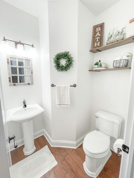 """Half Bath Update 🏡  Per usual, I forgot to take a good """"Before"""" photo, but you can swipe through to see what it looked like a couple years ago.   I replaced a dark medicine cabinet behind the toilet with DIY floating shelves and hidden storage in baskets and canisters. Eventually I plan to replace the mirror for something more useable, but for now the one that came with the house can stay.   The shelf brackets are linked at shop.erindavisonphoto.com  #LTKhome #LTKfamily #StayHomeWithLTK"""