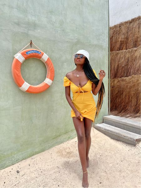 Beach Vacation outfit. Yellow orange puff sleeve cut out dress and white bucket hat.   #LTKstyletip #LTKunder50 #LTKtravel