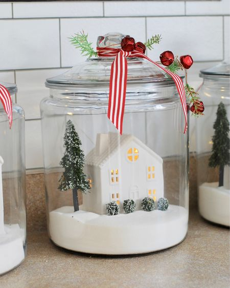 """With Christmas comes touches of magic and these jars are just that. The tiny glow inside the white houses with the festive stripe red ribbon, makes these jars darling, festive and super easy to put together. These particular jars where published in @betterhomesandgarden in """"Christmas Ideas"""" edition back a few years ago. I thought before all the shopping is done, I would give you a list of supplies for this darling decor.  I was so excited when I found the perfect place for them in my kitchen. I'm so glad I broke out these jars again after not using them for the past few years. They are a crowd favorite for sure. I have everything linked for you on #LTKholidayathome #LTKholidaystyle #LTKholidaygiftguide   Merry Christmas Everyone!   http://liketk.it/2Ip9x #liketkit @liketoknow.it"""