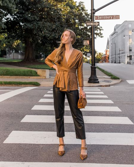 Fall date night inspiration 🍂 Wearing S in tan blouse, faux leather pants are Levi's ribcage (sold out, two similar linked). Pumps are old Ann Taylor (two similar linked). Suede pouch comes in three neutral colors!  For 5 more fall date night outfits, visit natalieyerger.com!  #FallDateNight #FallDateNightOutfits, #WrapTop #LeatherPants #LeatherPantsOutfit #FauxLeatherPants #TanBlouse #DateNightFall