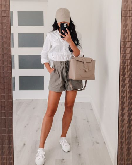 how to style khaki olive green shorts for the summer with a white button up top and white sneakers   Button up top (wearing size small) Shorts (wearing size medium) Sneakers (wearing size 37) Handbag is the MIDI size   #LTKstyletip #LTKshoecrush #LTKSeasonal