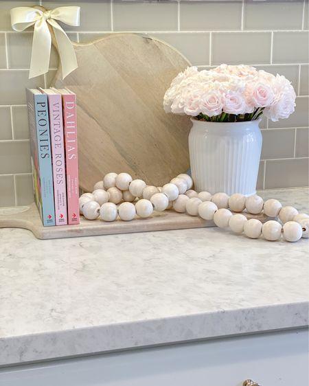 http://liketk.it/3azeW  Spring Decor  Kitchen Counter Decor Pink Books Wood Beads Whitewash cutting board  Charcuterie board Faux florals  #liketkit #LTKstyletip #LTKhome #LTKSeasonal @liketoknow.it @liketoknow.it.home