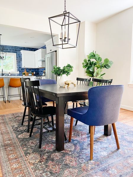 Love the mix and match dining chairs with the simple wood dining table.  Windsor chairs, wood dining table, dining room decor, lantern chandelier, blue dining chairs, Loloi rugs  #LTKhome