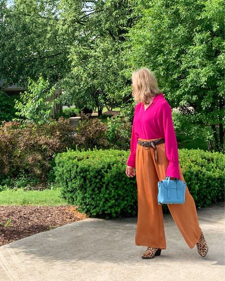 Here's one way to wear these cognac amber palazzo pants from Ann Taylor. (Get 50%off with code: CYBERSUMMER.) The color is bright and almost metallic and will work with just about any color you like! Pair them with a bright colored blouse and another pop of color with your handbag. I'm wearing a bright pink blouse with a sky blue Pashli mini satchel. My belt is in dark brown woven leather and the mules leopard calf hair adding some texture to the flat solid colors in this look.   #LTKstyletip #LTKsalealert #LTKSeasonal