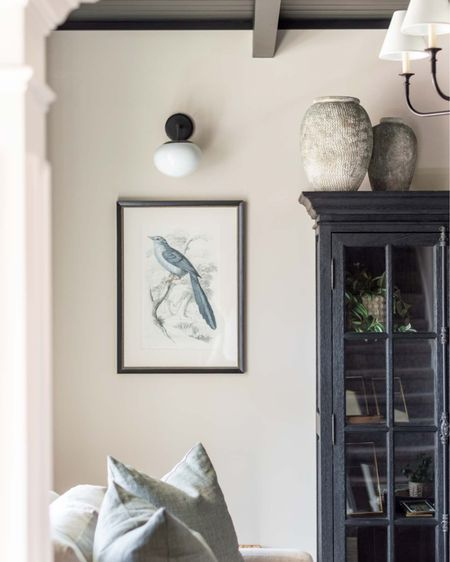 Our conversation room updat is almost complete!  http://liketk.it/3cnq2 #liketkit @liketoknow.it #LTKhome #LTKstyletip home decor sitting room decor living room decor bird print pair black curio cabinet black single arm sconce iron chandelier pottery barn loveseat sage green linen pillow cement vase