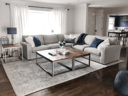 I love neutral decor with a pop of navy and I was so happy that this was the direction my clients wanted to go in! Didn't their living room come out amazing?  Since the couch they picked from Pottery Barn was so large and they had such a large amount of empty space in the room to fill, we opted for a double coffee table and I'm loving it! This look can be achieved by ordering two of almost any rectangular coffee table and positioning them together as one. I'm really loving the rustic finish with the navy accents as well.  I'd also like to draw your attention to the sneak peak of their almost finished dining room in the background! I'm so excited to share that space with you guys as well; spoiler alert we used my absolute favorite navy blue grass cloth wall paper from Serena and Lily and it is fantastic!  I'm sharing most of the products on @liketoknow.it  although we did find some items at homegoods so I substituted in similar items in #liketkit . http://liketk.it/3bgnk