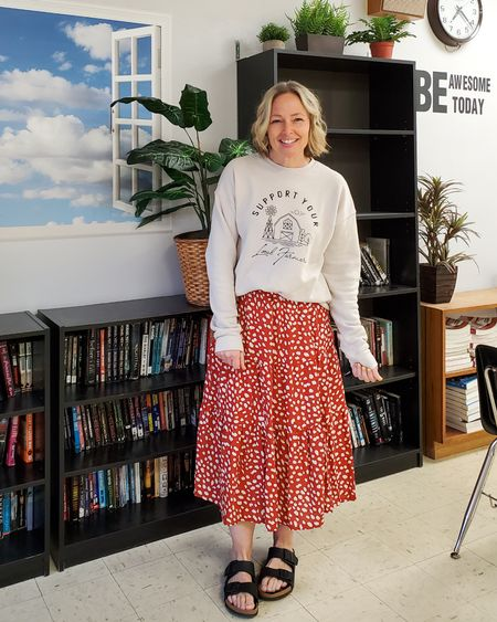 Casual everyday spring teacher outfit featuring a graphic sweatshirt, floral animal print ruffled tiered midi skirt, and Birkenstocks #teacher #supportlocalfarmers #shoplocal #local #roolee #midiskirt #tieredskirt #ruffleskirt #birkenstocks #casual #spring #petite #lifestyle http://liketk.it/3dm84 @liketoknow.it #liketkit