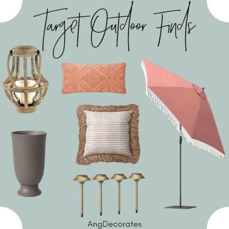 Target Outdoor Finds: pink fringe umbrella, beaded wood lantern, urn planter, gold solar lights, and outdoor throw pillows  #LTKSeasonal #LTKhome #LTKunder100