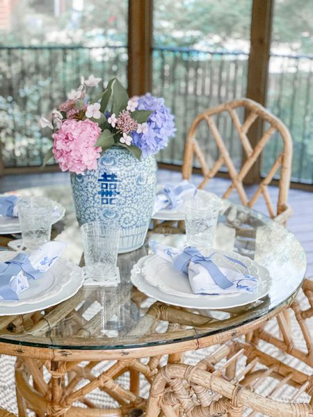 Outdoor patio furniture dining table setting tablescape blue and white chinoiserie Ginger jar grandmillennial vase hydrangeas bow napkin rings Hilk house home napkins rattan furniture home decor coastal Serena and Lily dining set chairs bamboo natural   #LTKfamily #LTKhome #LTKunder100