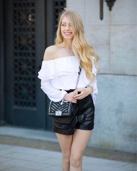 Black leather shorts White flowy off the shoulder top Black leather sandals mid heel Chanel small boy with pearls  Spring summer edgy classic style  #LTKstyletip #LTKunder100 #LTKSeasonal