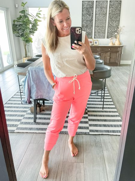 Love these neon coral joggers which come in other colors and on and are on sale for only $17 right now. Cute with this oatmeal colored muscle tank top. Wearing a size small both and they other colors. Loft sale summer loungewear joggers travel outfit  #LTKunder50 #LTKsalealert #LTKSeasonal