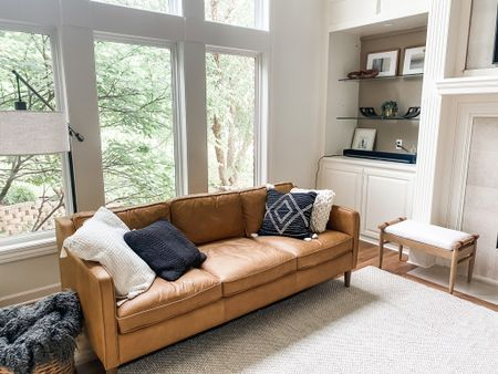 Some more living room details! #home #homedecor #interiordesign #leathercouch #arearug #neutrals #pillows#throwpillows #camel #art #target #inexpensive   #LTKhome #LTKunder50 #LTKfamily