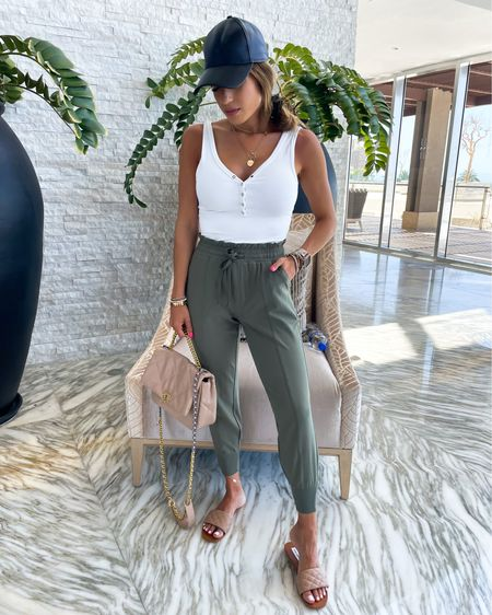White bodysuit in Xs joggers in xxs short faux leather baseball cap bag 15% off with SAMANTHA15 nude sandals 30% off on sale with code belbel. Travel outfit look  #liketkit @liketoknow.it http://liketk.it/3hXTg #LTKtravel #LTKsalealert #LTKunder100