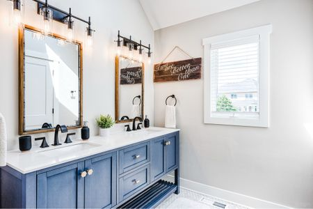 """The girls' bathroom renovation:  after/after/before/before  This bathroom was a fun transformation!  We gutted this baby, just like most of the rest of the house.  We ended up pulling out the original vanity and long strip of bulb lighting and opting for more of a furniture piece for the double vanity.  We actually got the double vanity from @Wayfair !  The color is technically """"charcoal grey"""" but is definitely looks navy blue in person - which is what I was going for.  It has a white quartz countertop and we made it our own by adding the @cb2 gold hex knobs and pulls and the black @kohler widespread faucets.  Mixing metal is a fun way to make your space unique!  The gold ties in with the rest of the house and the black, also featured in the lights and accessories makes it unique.  The wooden/metal mirrors add some warmth to the bathroom, that can otherwise feel kinda cold.   Other updates:  We ripped out the old glass surround shower and tub and built out a raw edge grey subway tile wall and surround with an oversized tub.  We also enclosed the toilet and made a water closet so that there'd be privacy for the girls as they get older.  The skylight adds a lot of natural light and we had new trim framed out around the window for extra brightness.  The hex mosaic grey/white tile is a fun design element that also gives a lot of grip for those slippery little feet.  We already have so many bathtub dance parties and can't wait for the girls to grow into this year after year.  Everything is linked - from the light fixtures down to the bathmats - right here: http://liketk.it/30ved  //also linked on the @liketoknow.it app under my IG name!   #bathroomdesign#bathroomdesigns #homereno#homerenovation #liketkit  #LTKhome #beforeandafter#interiordesign#bathroom#bathroombeforeandafter#kidsbathroom#bathroomtransformation#homerehab#interiors#design#interiorideas#homedesign#transformation#hometransformation#chicagoblogger#homeaccents#homedecor #LTKkids"""