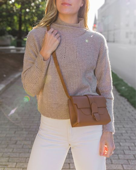 Cashmere sweater (size S) with brown belt bag (can also be worn crossbody), white wide leg jeans (TTS) and Dior lip balm in Rosewood.  #womensfalloutfits #tansweater #leatherbeltbag #brownbeltbag #senreve #bloomingdales #mocknecksweater #beigesweater #cashmeresweater