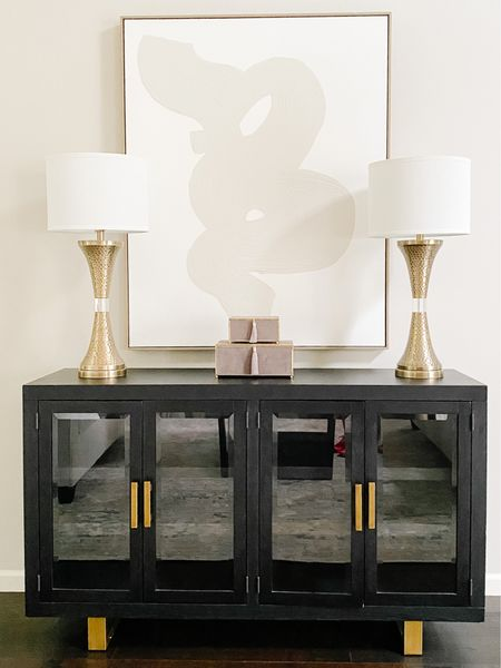 Love the neutral art above the modern black media cabinet.  Media console, black cabinet, accent furniture, storage furniture, gold lamps, brass lamps, neutral art, living room decor, dining room decor  #LTKhome