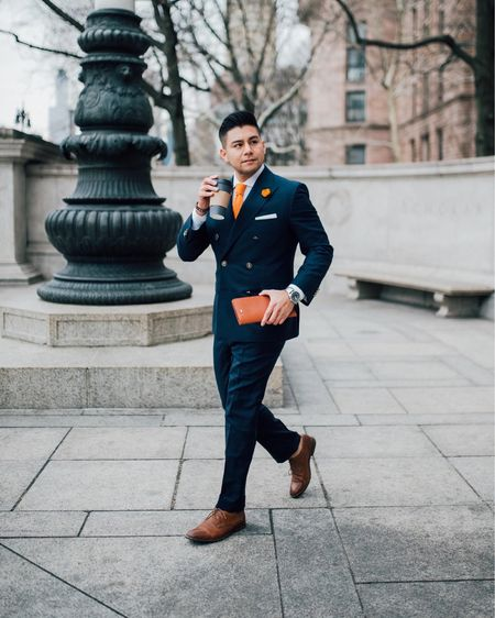 """Here I am wearing a custom navy suit with orange accessories. If you don't know how to combine colors, look towards sport teams and flags! Let's look at The Bronx's flag. 🧡🤍💙  The Bronx (always """"The Bronx"""", never just """"Bronx"""") flies a flag of three horizontal orange-white-royal blue stripes with the Borough Seal on a white disc in the center, overlapping the upper and lower stripes. The Bronx borough flag was adopted in 1912. It is described as the Dutch colonial flag (the Prinsenvlag of orange, white, and blue horizontal stripes), with the addition of the Bronck family arms encircled by a laurel wreath denoting honor and fame. The shield shows the face of the sun with rays displayed rising from the sea, signifying peace, liberty, and commerce. I'll have a picture in my stories.  Stay informed, Stay Dandy  http://liketk.it/33yTQ #liketkit @liketoknow.it #LTKworkwear #LTKmens  orange tie, orange knitted tie, navy suit , orange accessories, men's style , men's orange tie"""