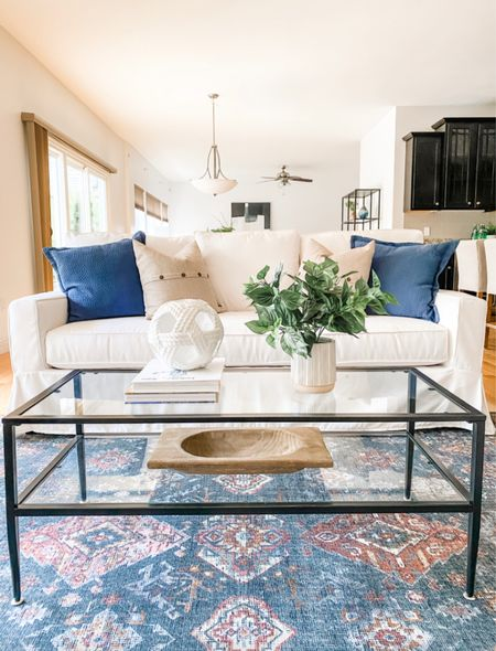 White slipcovered sofa with a colorful area rug and black metal coffee table.  Living room decor, home decor, white sofa, glass coffee table, slip cover  #LTKhome