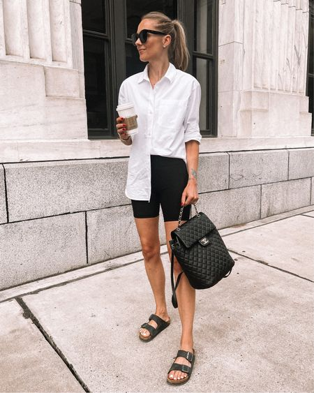 This white button up shirt is so versatile and I love it paired with black biker shorts! Wearing an XS use code JACKSON15 for a discount #sandals #chanelbackpack  #LTKshoecrush #LTKstyletip #LTKunder100