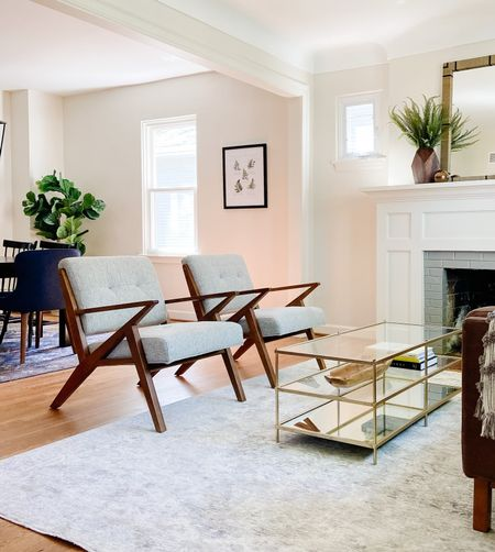 A pair of midcentury modern lounge chairs keep an open feeling the living room.  Living room decor, living room chairs, accent chairs, mid century furniture, brass and glass coffee table, home decor  #LTKhome