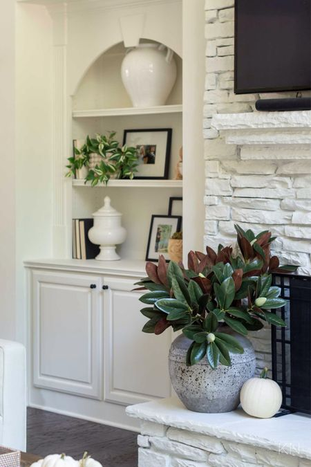 These faux magnolia branches add the perfect fall touch to my living room decor. Home decor large stone vase built in styling fall decor fall branches  #LTKhome #LTKstyletip #LTKSeasonal