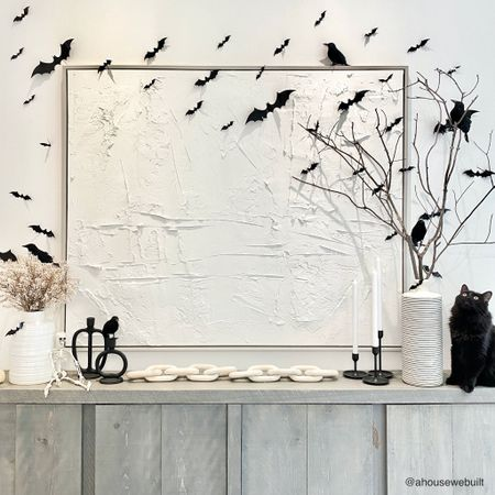 Our dining room Halloween decor is complete! I used my favorite bats (attached with scotch tape), black birds and skeletons, and paired them with decor pieces that I felt could fit a spookier theme. I had to literally sit on our dining table to get this straight-on pic but it's the angle that shows everything best. And how cute is our rescue kitty Nyx checking it all out?? — Shop your screenshot of this pic with theShop.LTK app